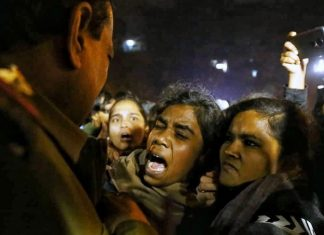 Students protest outside the JNU main gate while a policeman restrains them