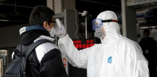 A worker in a protective suit checks the temperature of a man in Beijing. WHO has declared coronavirus outbreak a global health emergency.