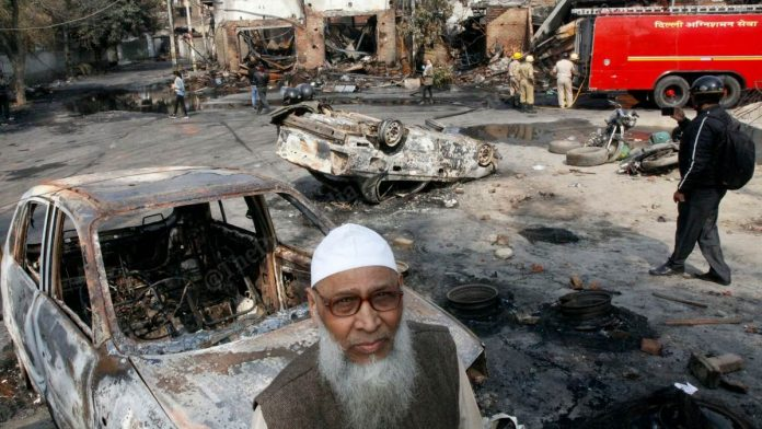 A man stands amid the burnt-out ruins of the Gokulpuri tyre market in Northeast Delhi | Photo: Praveen Jain | ThePrint