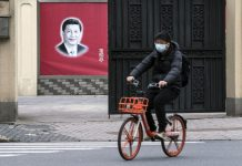 A cyclist wearing a protective mask rides past a banner of Chinese president Xi Jinping in Shanghai | Qilai Shen/Bloomberg