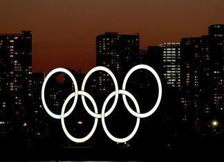 The sun sets behind the Olympic rings installation at Odaiba Marine Park on March 18, 2020 in Tokyo, Japan   Photographer: Clive Rose/Getty Images AsiaPac   Bloomberg