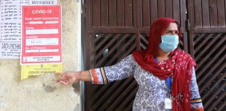 An ASHA worker, pastes a Covid-19 isolation poster outside a patient's house | Manisha Mondal | ThePrint