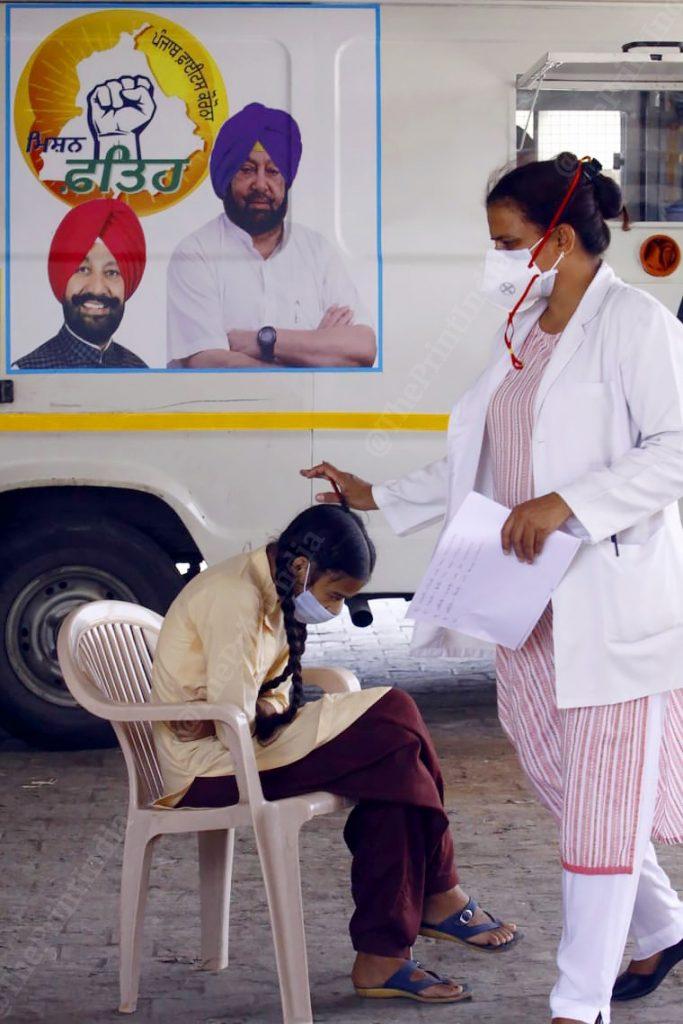 A nurse on sampling duty blessing a young girl in Bakarpur village ahead of her turn for COVID—19 testing | Praveen Jain | ThePrint