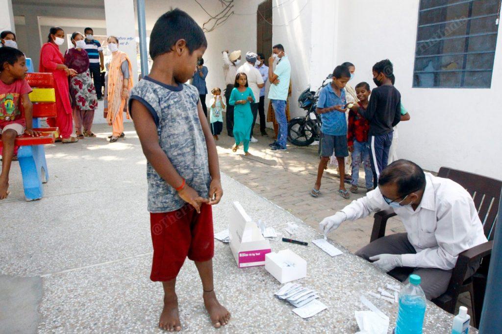 A young kid looking at the testing kid in Sahnewal village | Praveen Jain | ThePrint