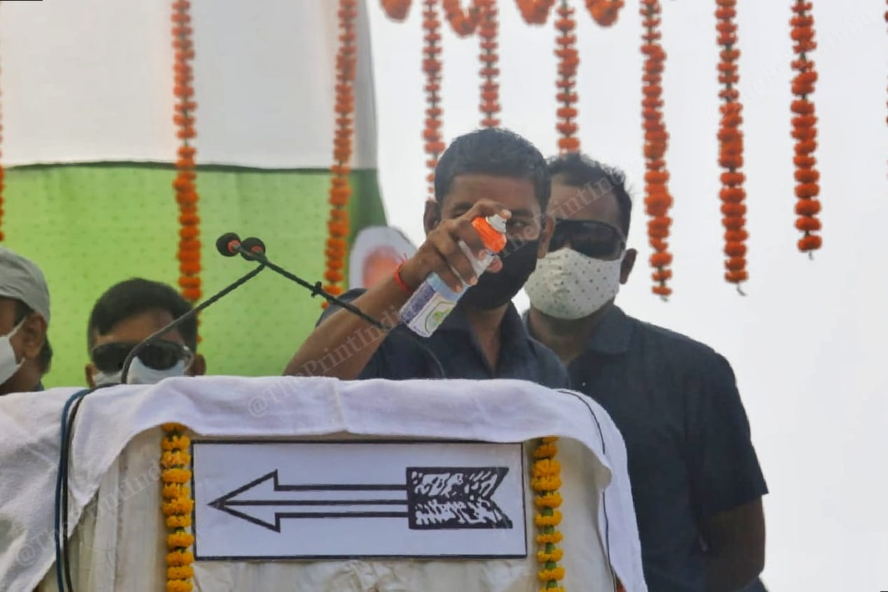 A security personnel sprays sanitiser on the podium and the mic before the chief minister's speech | Photo: Praveen Jain | ThePrint