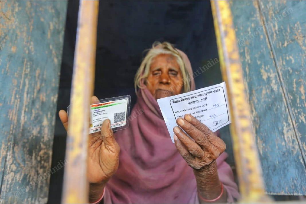 An elderly woman stands holding her Voter ID card in Belhori village | Praveen Jain | ThePrint