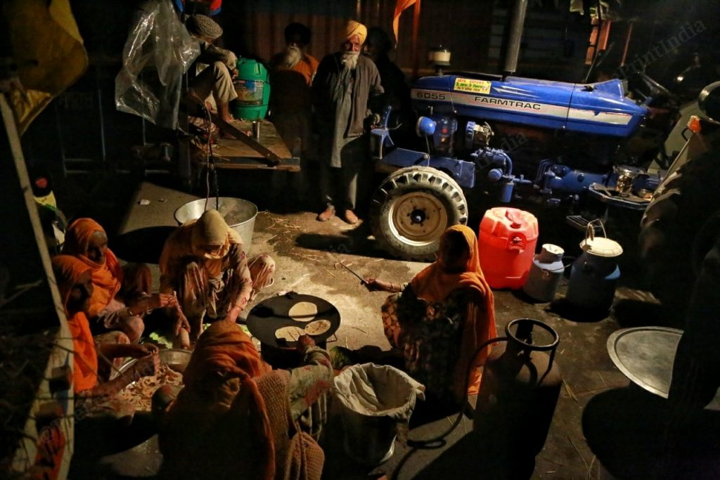 Farmers serving food, while women make chapattis | Photo: Manisha Mondal | ThePrint
