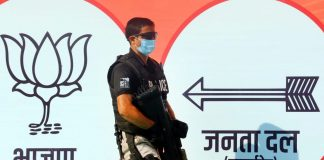 A Special Protection Group personnel stands between the party banners of BJP and JD(U) | Photo: Praveen Jain | ThePrint