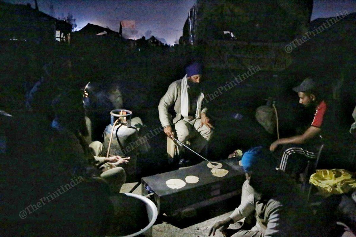 A group of farmers chant Satnam Waheguru Ji while preparing dinner | Photo: Manisha Mondal | ThePrint