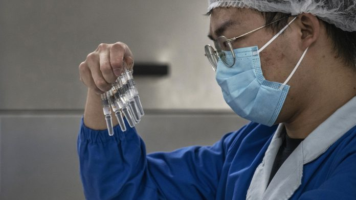 A worker checks syringes of a potential vaccine CoronaVac on the production line at Sinovac Biotech in Beijing on 24 September