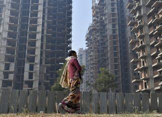 File image of a woman walking past buildings under construction in Noida, Uttar Pradesh | Photo: Anindito Mukherjee/Bloomberg