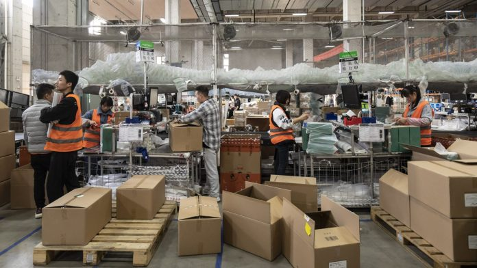 Employees pack orders at Alibaba's logistics arm Cainiao in Wuxi ahead of the Singles' Day shopping extravaganza | Bloomberg