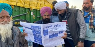 Farmers at Delhi's border reading a copy of the first edition of bi-weekly newsletter Trolley Times. | Photo: Revathi Krishnan/ThePrint